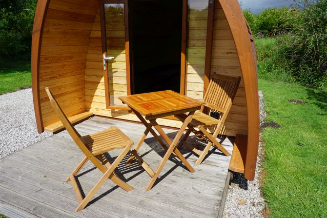 The decking, table and chairs of a camping pod at Woodland Springs